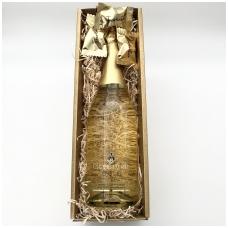 Putojantis vynas su aukso dulkėmis ir saldainiais dėžutėje